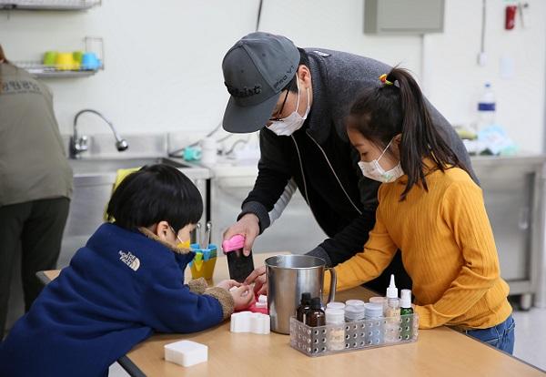 한 가족이 재활용 체험 프로그램에 참가해 만들기를 하고 있다.