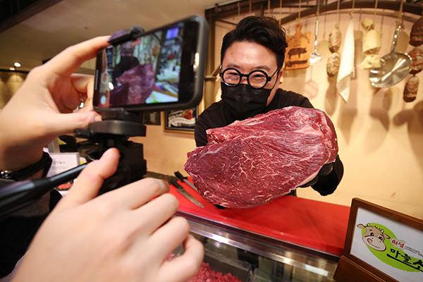 정육 담당자가 영상과 채팅을 통해 실시간으로 고객의 궁금증을 풀어주고 소통하는 '라이브커머스'를 통해 소고기를 판매하고 있다.(사진=저작권자(c) 연합뉴스, 무단 전재-재배포 금지)