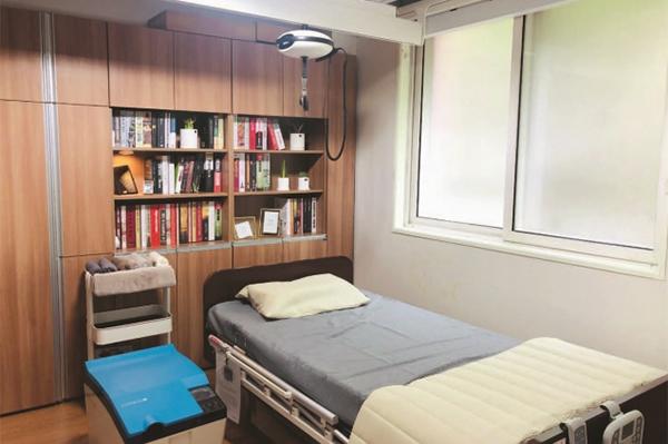'천장 주행형 리프트'와 '전동 베드' 및 이동 가능한 '배설 보조장치'가 설치된 침실.