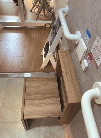 현관 벽에 설치한 접이식 의자와 손잡이.