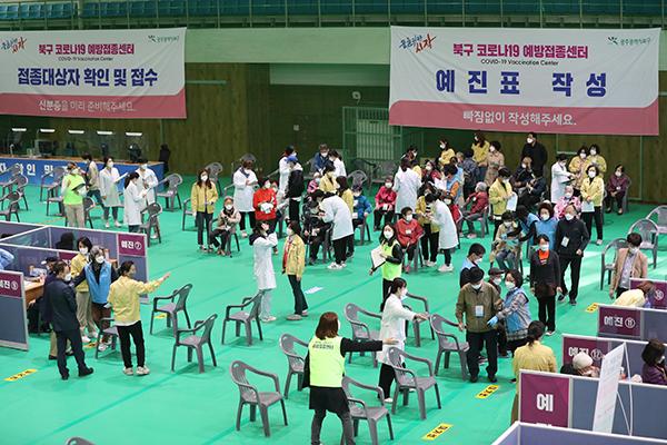 광주 북구 예방접종센터에서 75세 이상 어르신들이 북구청 공무원과 자원봉사자들의 도움을 받아 이동하고 있다.