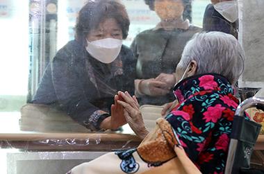 광주 동구 강남요양병원에서 90대 입원 환자와 딸이 비대면 면회를 하던 중 투명 가림막을 사이에 두고 손을 마주대고 있다.