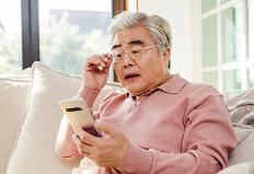 휴대폰을 보고 있는 어르신