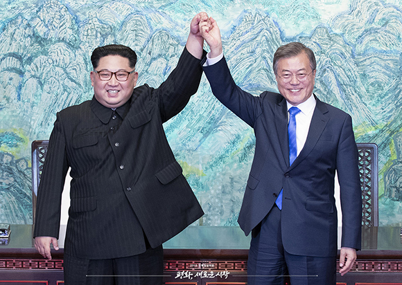 문재인 대통령과 김정은 위원장이 2018년 4월 27일 '판문점 선언문'에 서명한 뒤 손을 들어 보이고 있다.