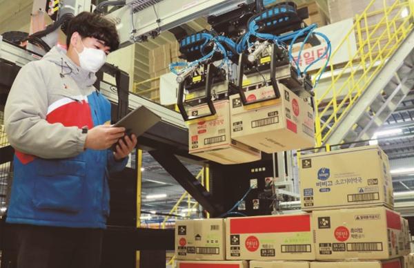 택배 박스의 면적과 높이, 위치를 인식해 자동으로 컨베이어벨트에 옮기는 '인공지능(AI) 로봇 디팔레타이저'를 이용해 박스를 옮기는 CJ대한통운 직원.(사진=저작권자(c) 연합뉴스, 무단 전재-재배포 금지)