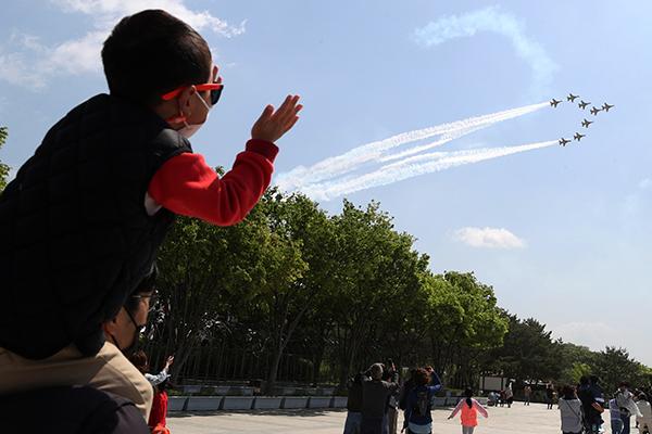 제99회 어린이날이었던 지난 5일 충남 천안 독립기념관에서 아빠 목말을 탄 한 어린이가 공군 특수비행팀 '블랙이글스' 축하비행을 보며 즐거워하고 있다.
