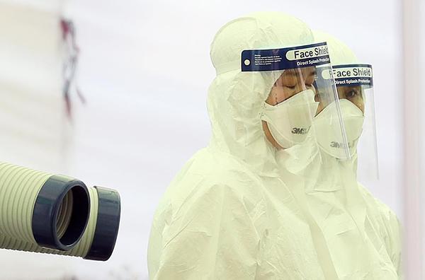 지난해 6월 서울 강서구보건소 선별진료소에서 의료진과 관계자들이 코로나19 검체 검사를 위해 방역복을 입고 낮 최고 기온 30도까지 오르는 무더위와 사투 중이다.