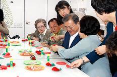 문재인 대통령과 부인 김정숙 여사가 2019년 5월 7일 오전 금천구 치매안심센터를 방문, 치매 어르신들과 함께 종이접기로 카네이션을 만들고 있다.
