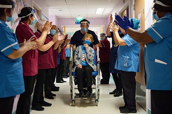 2020년 12월 8일(현지시간) 영국에서 미국 제약사 화이자와 독일 바이오엔테크가 공동 개발한 코로나19 백신을 세계 최초로 접종한 90세의 마거릿 키넌 할머니가 휠체어에 탄 채 코번트리의 대학병원 복도를 지나가며 의료진의 박수를 받고 있다.