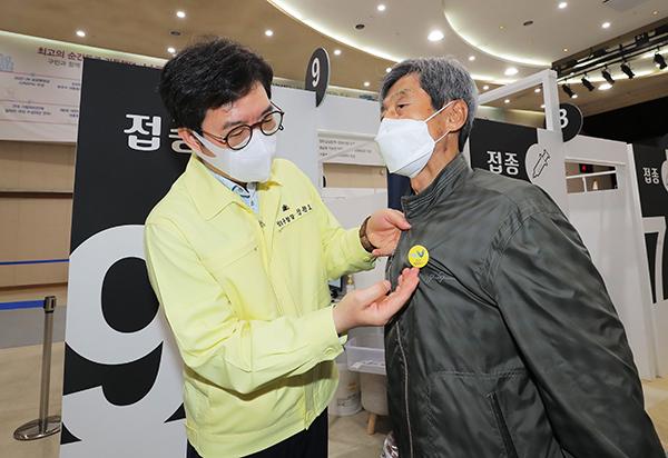 정원오 성동구청장이 지난 22일 오전 서울 성동구청에 설치된 서울시 1호 코로나19 예방 접종 센터에서 2차 접종을 마친 한 어르신에게 안심배지를 달아드리고 있다.