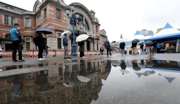 21일 서울 중구 서울역광장에 마련된 신종 코로나바이러스 감염증(코로나19) 임시 선별검사소에서 우산을 쓴 시민들이 검사를 기다리고 있다.(사진=저작권자(c) 뉴스1, 무단 전재-재배포 금지)