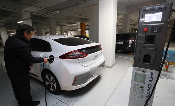 세종시 한 아파트 단지 주차장에 설치된 전기차 충전소에서 한 주민이 자신의 전기차를 충전하고 있다.