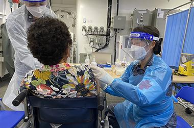 지난 21일 전남 진도 인근 해상에 정박한 해군 한산도함 내 격납고에 마련된 코로나19 예방접종센터에서 동거차도 주민이 백신 접종을 맞고 있다.
