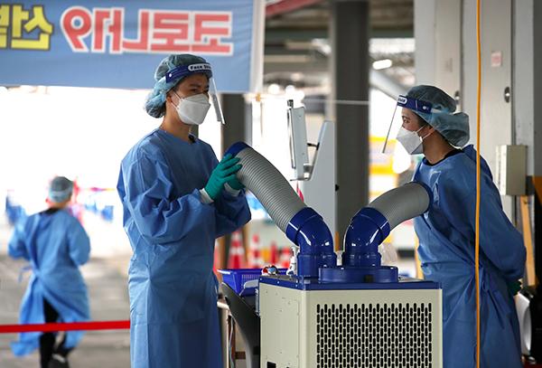 낮 기온이 30도 안팎의 초여름 날씨를 보인 광주 북구보건소 선별진료소에서 의료진들이 냉풍기로 더위를 식히고 있다.