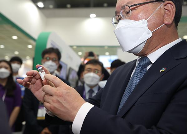 김부겸 국무총리가 9일 서울 코엑스에서 열린 바이오 코리아 2021 개막식에 참석해 전시 부스에서 임상 시험 중인 백신을 보고 있다.