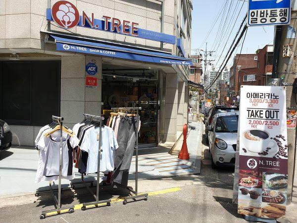 동네 골목길 모퉁이에 커피점과 의류점이 결합된 매장이 있다.