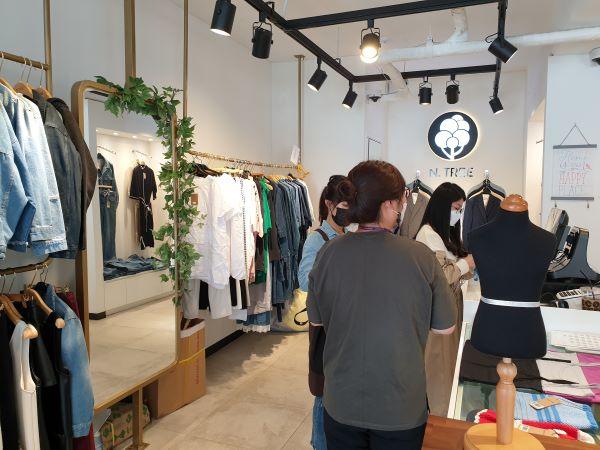엔트리(N.TREE) 매장을 방문한 손님이 옷을 구입하고 있다.