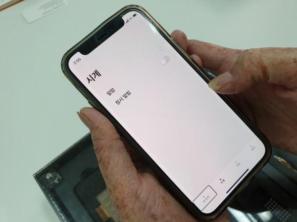 시각 장애인이 스마트워치와 연결된 스마트폰을 사용하고 있다.
