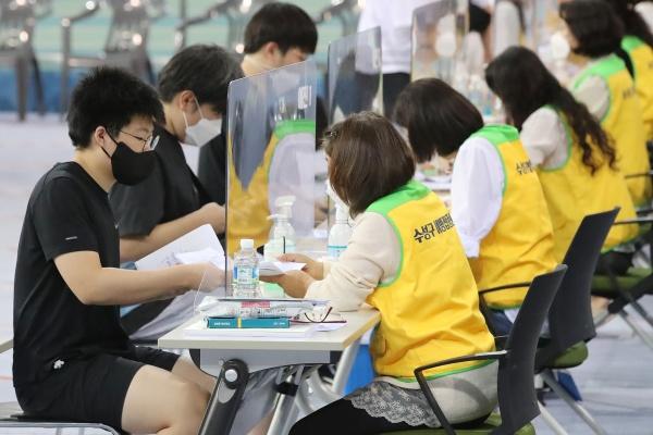 수능을 앞둔 고등학교 3학년과 교직원 등에 대한 코로나19 화이자 백신 1차 접종이 시작된 19일 오전 대구육상진흥센터에 마련된 수성구 예방접종센터에서 고3 학생들이 예진을 받고 있다.