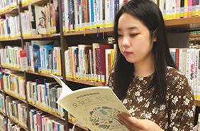 자신이 그린 컬러링북 <오늘도 안녕!>을 바라보는 허승희 작가.