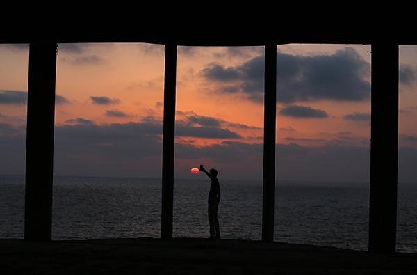 가자지구 남쪽의 알 모그라카 인근 해질녘 바다 앞. (사진=EPA/저작권자(c) 연합뉴스, 무단 전재-재배포 금지)