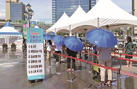 서울역 임시 선별검사소에서는 대기하는 시민들이 조금이나마 더위를 피할 수 있도록 그늘막을 설치하고 양산을 대여하고 있다.