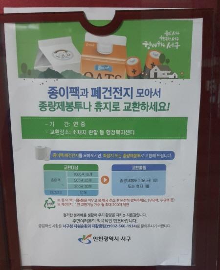 아파트 게시판에 붙은 홍보물, 폐건전지와 종이팩을 모아가면 종량제봉투나 휴지로 교환할 수 있다.