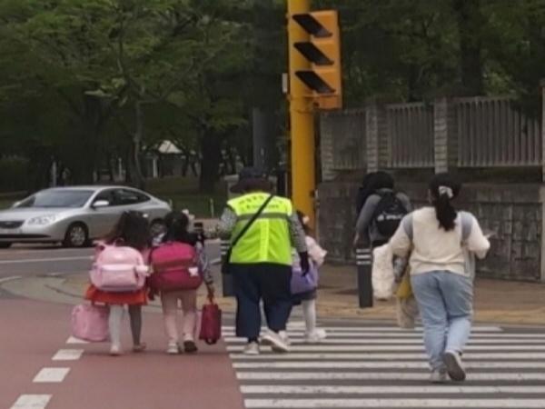 한 초등학교 앞에서 교통 봉사를 하시는 어르신
