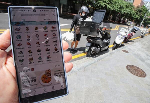 배달업체 관계자가 배달할 음식을 오토바이에 싣고 있는 모습.(사진=저작권자(c) 연합뉴스, 무단 전재-재배포 금지)