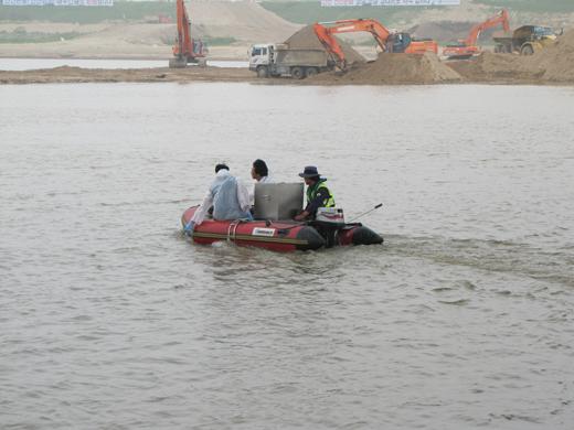 한미공동조사단 관계자들이 보트를 타고 하천수 시료를 채취하고 있다.