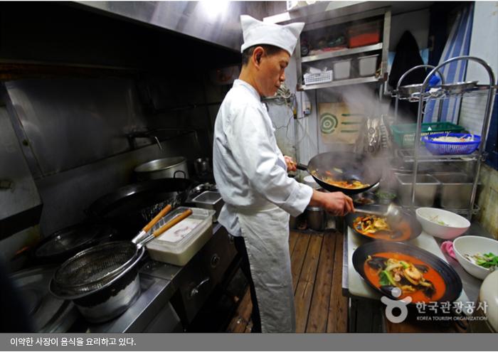 이약한 사장이 음식을 요리하고 있다.