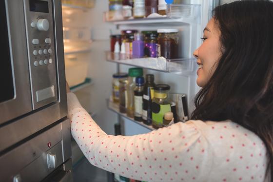 냉장고 안을 들여다보고 있는 여자.