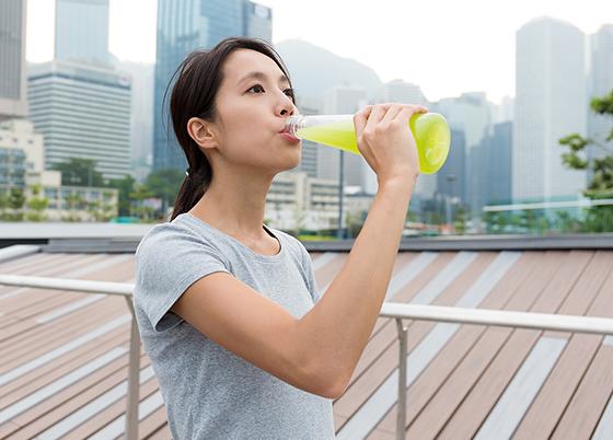 운동 중 이온음료 마시는 여자.