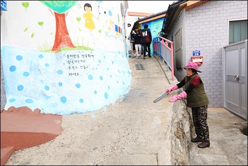 관광객들이 버린 쓰레기를 청소하고 있는 동피랑 주민 안외선씨